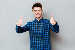 Young happy man holding thumbs up. Young happy man wearing casual holding thumbs up stock photos