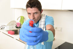 Young happy man holding washing detergent spray bottle as aiming with hand gun playful Stock Photos