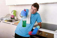 Young happy man holding washing detergent spray bottle as aiming with hand gun playful Stock Image