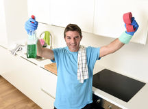 Young happy man holding washing detergent spray bottle and sponge in gloves smiling confident. Young attractive and happy man holding washing detergent spray royalty free stock images