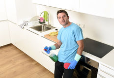 Young happy man holding washing detergent spray bottle and sponge in gloves smiling confident. Young attractive and happy man holding washing detergent spray stock photos