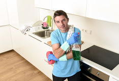 Young happy man holding washing detergent spray bottle and sponge in gloves smiling confident. Young attractive and happy man holding washing detergent spray royalty free stock image