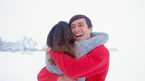 Young happy man hugging his girlfriend. Emotional couple in love hugging at winter on snow background. stock footage