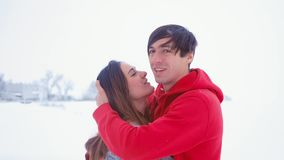 Young happy man hugging his girlfriend. Emotional couple in love hugging at winter on snow background. Meeting after a long separation stock video