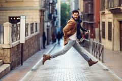 Young happy man jumping wearing winter clothes in urban backgrou Royalty Free Stock Photography