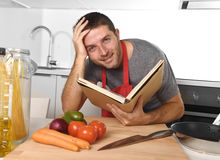 Young happy man at kitchen reading recipe book in apron learning cooking Royalty Free Stock Image