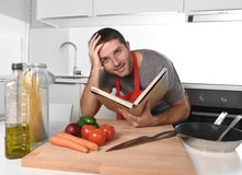 Young happy man at kitchen reading recipe book in apron learning cooking Stock Photo