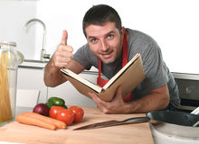 Young happy man at kitchen reading recipe book in apron learning cooking Stock Images