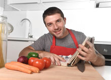 Young happy man at kitchen reading recipe book in apron learning cooking Stock Image