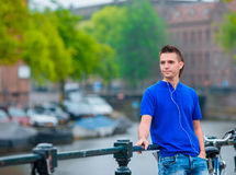 Young happy man listening to music background of canal in Amsterdam, Netherlands stock photo