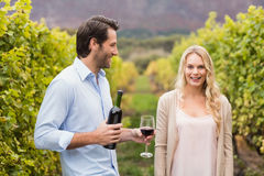 Young happy man offering wine to a young woman Royalty Free Stock Image