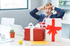 A young man in the office receives a gift. A young happy man in the office during business hours receives a gift from the ring. Many gifts. Close-up Stock Photography