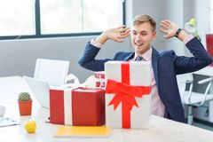 A young man in the office receives a gift. A young happy man in the office during business hours receives a gift from the ring. Many gifts. Close-up Royalty Free Stock Image
