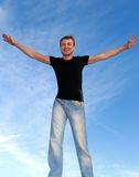 Young happy man with open arms outdoors. Over blue sky royalty free stock photography