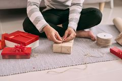 Young happy man packing Valentine gift while sitting on floor.  Stock Photos