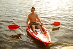 Young Happy Man Paddling Kayak on Beautiful River or Lake at Sunset. Young Happy Man Paddling Kayak on the Beautiful River or Lake at Sunset Stock Image