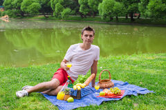 Young happy man picnicking and relaxing in the Royalty Free Stock Photography