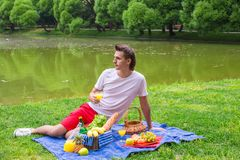 Young happy man picnicking and relaxing in the Royalty Free Stock Photos