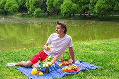 Young happy man picnicking and relaxing in the Royalty Free Stock Images