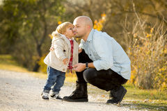 Young happy man playing with excited little cute son the child kissing his father stock photo