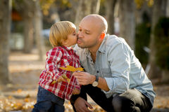 Young happy man playing with excited little cute son the child kissing his father Royalty Free Stock Image