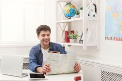 Young man reading map, planning vacation. Young happy man reading map at home. Handsome guy preparing for vacation, planning route of trip, copy space Stock Photography