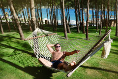 Young happy man Relaxing In Hammock in a garden with sea view. Young handsome man Relaxing In Hammock and smiling in a green garden Royalty Free Stock Image