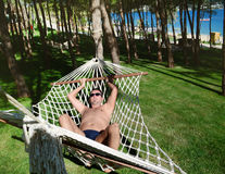 Young happy man Relaxing In Hammock. Young handsome man Relaxing In Hammock and smiling in a green garden Royalty Free Stock Photography