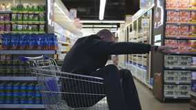 Young happy man riding inside shopping cart in hypermarket. Smiling guy sitting in supermarket trolley and going through. The store. Slow motion Close up stock footage