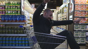 Young happy man riding inside shopping cart in hypermarket. Smiling guy sitting in supermarket trolley and going through. The store. Slow motion Close up stock video