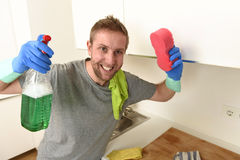 Young happy man in rubber washing gloves holding detergent cleaning spray and sponge smiling Royalty Free Stock Photo