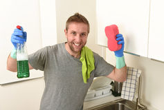 Young happy man in rubber washing gloves holding detergent cleaning spray and sponge smiling Royalty Free Stock Images