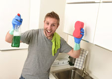 Young happy man in rubber washing gloves holding detergent cleaning spray and sponge smiling Stock Image