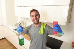 Young happy man in rubber washing gloves holding detergent cleaning spray and sponge smiling Royalty Free Stock Photography
