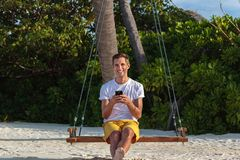 Young happy man seated on a swing and using his phone. White sand and jungle as background stock photography