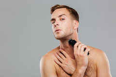 Young happy man shaving with electric razor Royalty Free Stock Photography