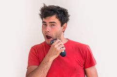 Young happy man shaving with electric razor Stock Images