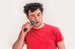 Young happy man shaving with electric razor Royalty Free Stock Photos