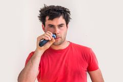 Young happy man shaving with electric razor Royalty Free Stock Photo