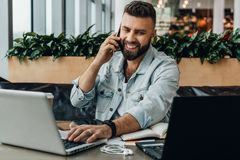 Young happy man sitting in office at table, working on computer, talking on phone.Freelancer has telephone conversations. Young bearded cheerful man sitting in stock image