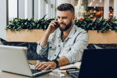 Young happy man sitting in office at table, working on computer, talking on phone.Freelancer has telephone conversations. Young bearded cheerful man sitting in royalty free stock photography