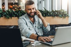 Young happy man sitting in office at table, working on computer, talking on phone.Freelancer has telephone conversations. Young bearded cheerful man sitting in stock photos