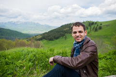 Young happy man sitting on the top of mountain and smile.  stock image