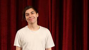 Young happy man smiling against red curtain background.  stock video