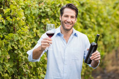 Young happy man smiling at camera and holding a glass of wine. In the grape fields Stock Photos