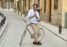 Young happy man smiling using mobile the phone on vintage cool retro bike Royalty Free Stock Photos