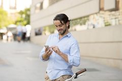 Young happy man smiling using mobile phone on vintage cool retro bike Stock Photos