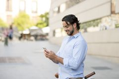 Young happy man smiling using mobile phone on vintage cool retro bike. Young happy attractive hispanic man in casual trendy clothes smiling cheerful using mobile royalty free stock photo