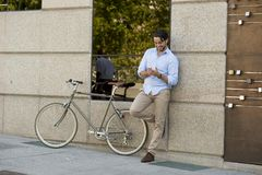 Young happy man smiling using mobile phone on vintage cool retro bike Stock Images