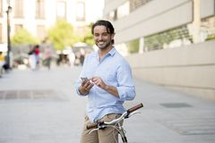 Young happy man smiling using mobile phone on vintage cool retro bike. Young happy attractive hispanic man in casual trendy clothes smiling cheerful using mobile royalty free stock photos